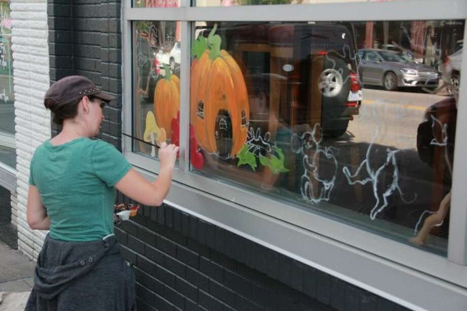 Local artist Michelle Chapman is helping Big Rapids get into fall by painting the outside windows at Artworks. Chapman also can be seen at Red Fox Market, in Morley and in Lakeview, painting business windows during the seasons and holidays. (Pioneer photo/Alicia Jaimes)