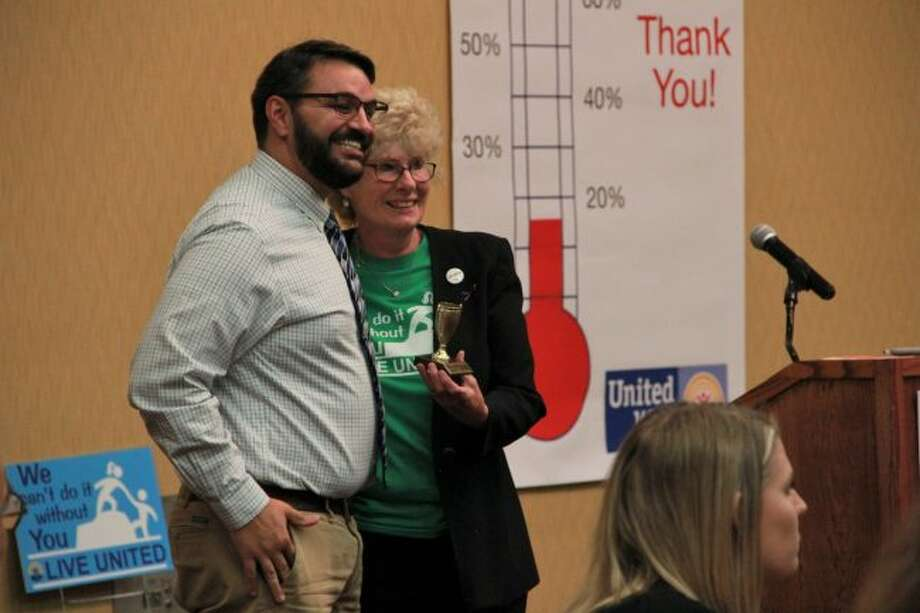 """Mecosta-Osceola United Way board member and """"web master"""" Nick Campau and Mecosta-Osceola United Way Executive Director Betty Seelye are all smiles as she hands him his Champion Trophy. These awards were given to people who gave United Way their all in the past year, according to Seelye. (Pioneer photo/Alicia Jaimes)"""