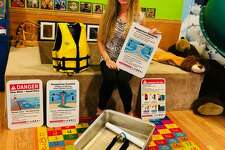 Executive director of Sandcastles Kristin Korendyke shows a working prototype for the wave table exhibit builders have been working with as well as some of the signs that will be displayed at the new Water Safety Exhibit the museum is planning for Spring of 2020. (Courtesy photo)