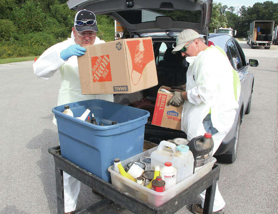 Employees of Wood River-based Heritage Environmental Services unload hazardous household waste during a collection Saturday at the Godfrey ball fields on Stamper Lane. Workers processed more than 350 loads of chemicals, ranging from oil-based paints to weed-killers during the event sponsored by Madison County Planning & Development.