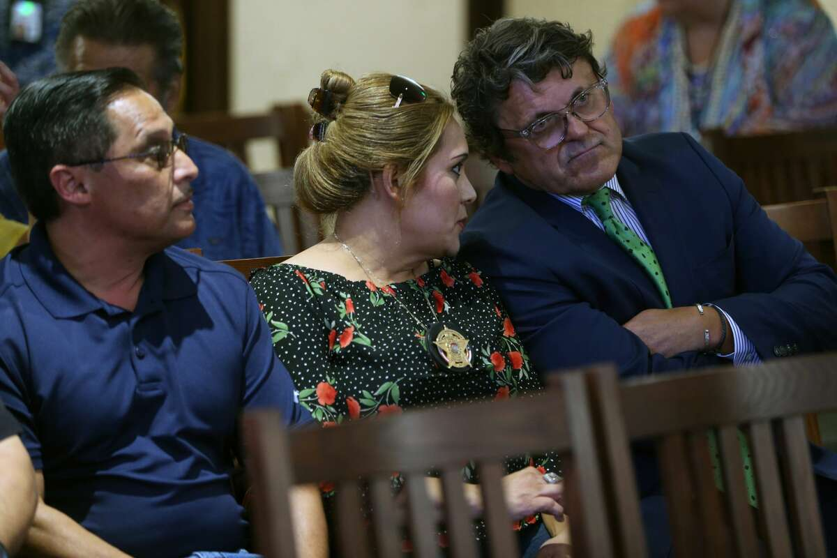 Bexar County Precinct 2 Constable Michelle Barrientes Vela, center, talks Wednesday, Sept. 25, 2019 with her attorney, Leslie JA Sachanowicz, during a news conference from County Judge Nelson Wolff. Wolff announced in the press conference that Vela's public statements indicating she would be running for sheriff triggered the state constitution's so-called resign-to-run clause and that the commissioners would be accepting applications to fill the position. Vela will remain in the position until the commissioners appoint a replacement according to Wolff. Vela's husband, Carlos Vela, is seen at left