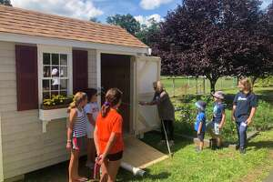 International School at Dundee students watch the unveiling of their new garden shed, recently inaugurated, which replaces a much smaller one and will provide much-needed functional space to support the students' work in the garden. The shed is a combined gift of the 2018 and 2019 5th grade classes, and students raised the money by selling wreaths.