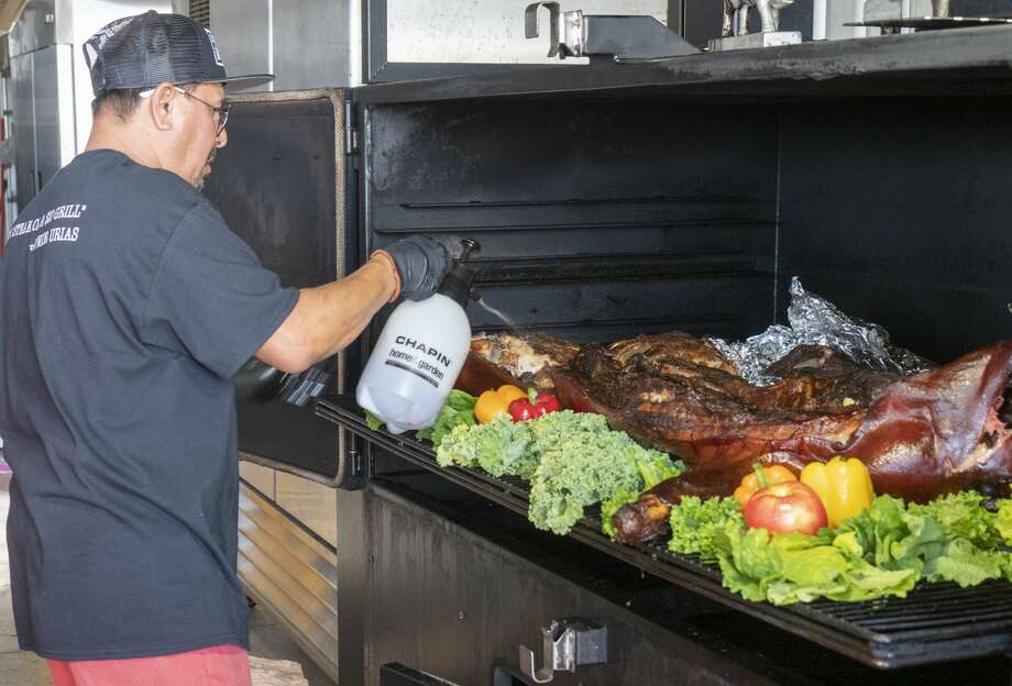Up in Smoke pit master Junior Urias prepares a whole hog on the pit on June 22. Photo: Tim Fischer/Midland Reporter-Telegram
