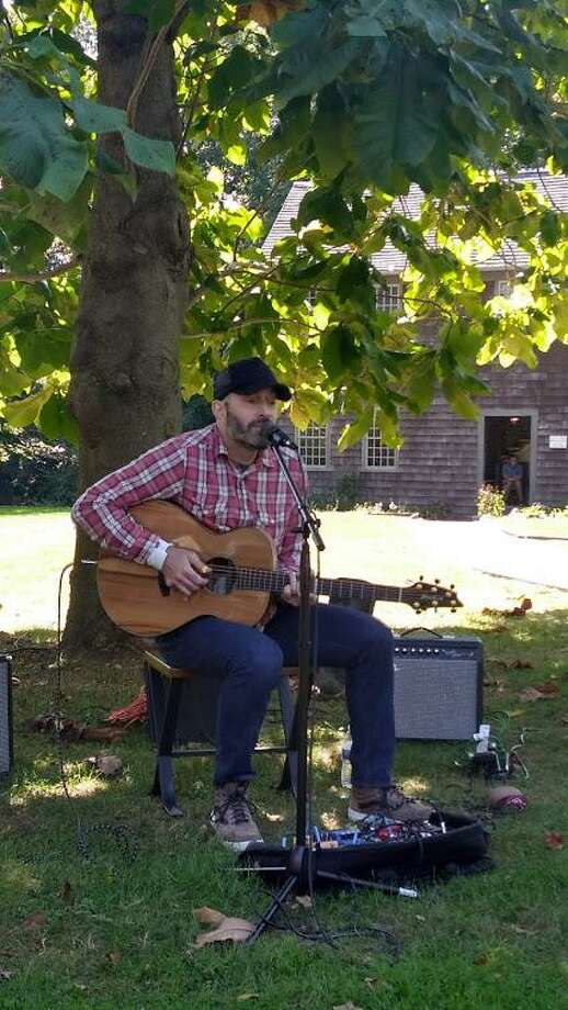 "Matt Jarrett, known as ""The Starving Viking,"" performs at the Milford Historical Society during last week's PorchFest. Matt is a member of MHS. In the background is the society's Stockade House, one of three historic houses at the MHS complex on High Street. Photo: Contributed Photo."