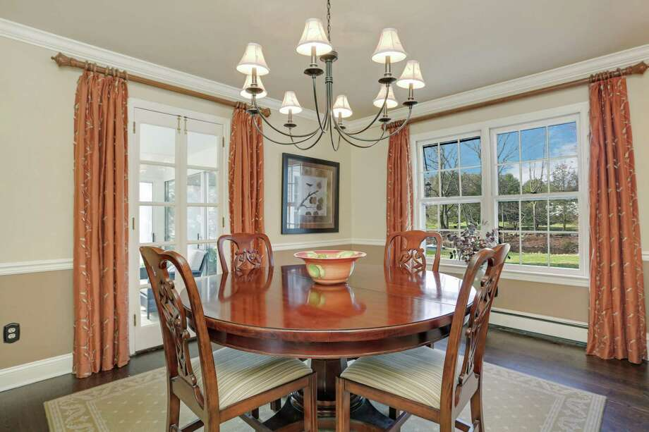 The formal dining room has chair railing and French doors to the enclosed porch.