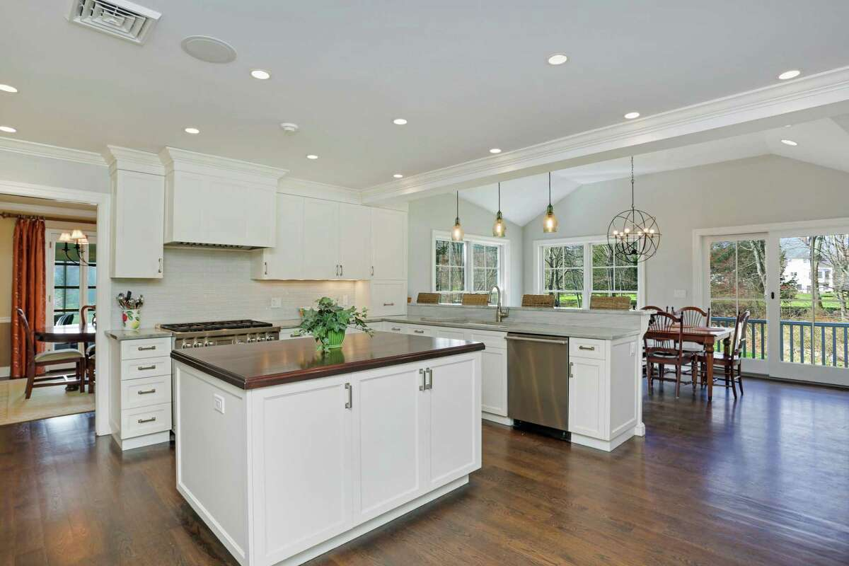 The kitchen features a center island, granite counters, a glass tile backsplash, a two-tiered breakfast bar, and Sub Zero and Wolfe appliances.