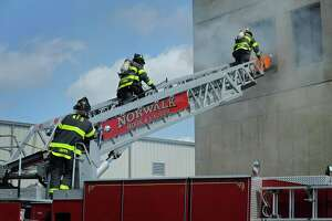 The Norwalk Fire Departments puts on a demonstration during The Norwalk Fire, DPW, Police, and EMS Open House and Touch-a-Truck event Saturday, September 29, 2018, at the Department of Public Works facility on South Smith Street in Norwalk, Conn.