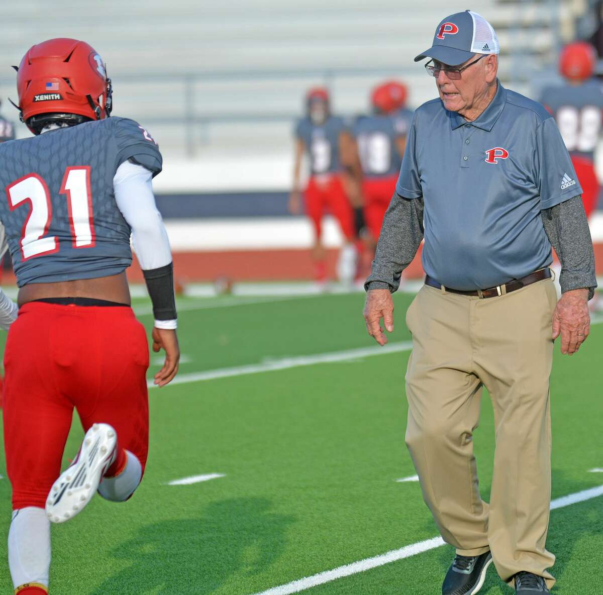Plainview assistant football coach Neil Billingsley encourages the players during warmups before the team's home game against Hereford on Friday in Greg Sherwood Memorial Bulldog Stadium.