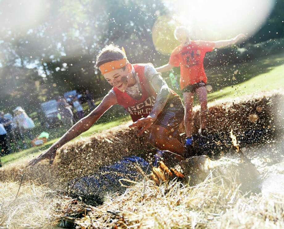 Greenwich's Zach Rohdie, 12, splashes in the mud pit near the finish line of the 8th annual Muddy Up 5K Run and Family Walk at Camp Simmons in Greenwich, Conn. Sunday, Sept. 29, 2019. Hundreds of participants ran through the course full of manmade obstacles including several mud pits. Proceeds from the event benefited the Boys & Girls Club of Greenwich. Photo: Tyler Sizemore / Hearst Connecticut Media / Greenwich Time