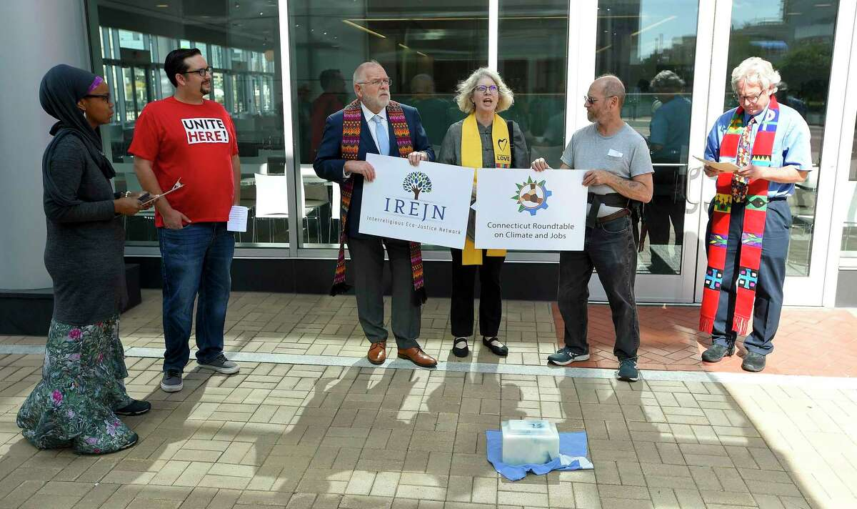 With an burial Urn containing ashes from Stamford-based Castleton Commodities' power plant in Bow. N.H. at their feet, religious leaders lead a regional campaign to shut down the last large coal-fired power plant operating in New England without a shut-down date, in front of Castleton Commodities offices in Stamford, Conn. on Sept. 24, 2019.