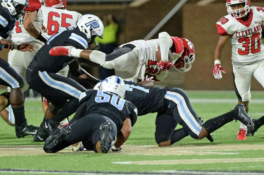 Tyreich Terry (12) of Cleveland is tackled by Luis Toscano (50) and Kamiron Hite (7) of Paetow during the second quarter of a 5A-2 Region III District 10 football game between the Paetow Panthers and the Cleveland Indians on Saturday, September 28, 2019 at Rhodes Stadium, Katy, TX. Photo: Craig Moseley, Houston Chronicle / Staff Photographer / ©2019 Houston Chronicle