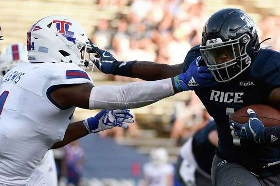Rice running back Aston Walter, right, fends off Louisiana Tech safety Darryl Lewis en route to a touchdown during the first half of an NCAA college football game, Saturday, Sept. 28, 2019, in Houston.