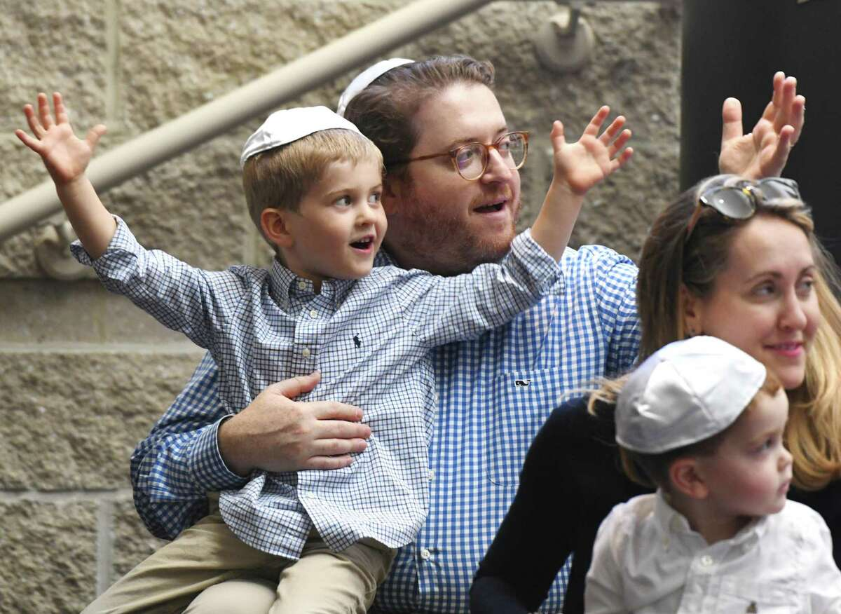 Greenwich's Joe Rothenberg sings songs with his son Max, 5, wife Marin, and son Henry, 2, during the Tot Rosh Hashanah service at Temple Sholom in Greenwich Monday. The program led by musical guest Sheldon Low and Rabbi Chaya Bender featured many fun singalongs for young children and their parents to celebrate the Jewish New Year.