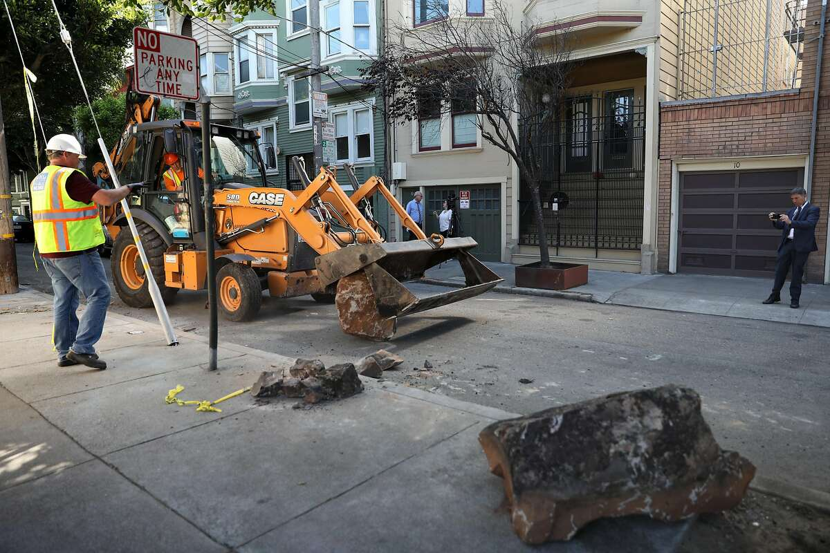 Public works removes boulders along the sidewalk along Clinton Park near Market at Dolores streets on Monday, Sept. 30, 2019, in San Francisco, Calif.