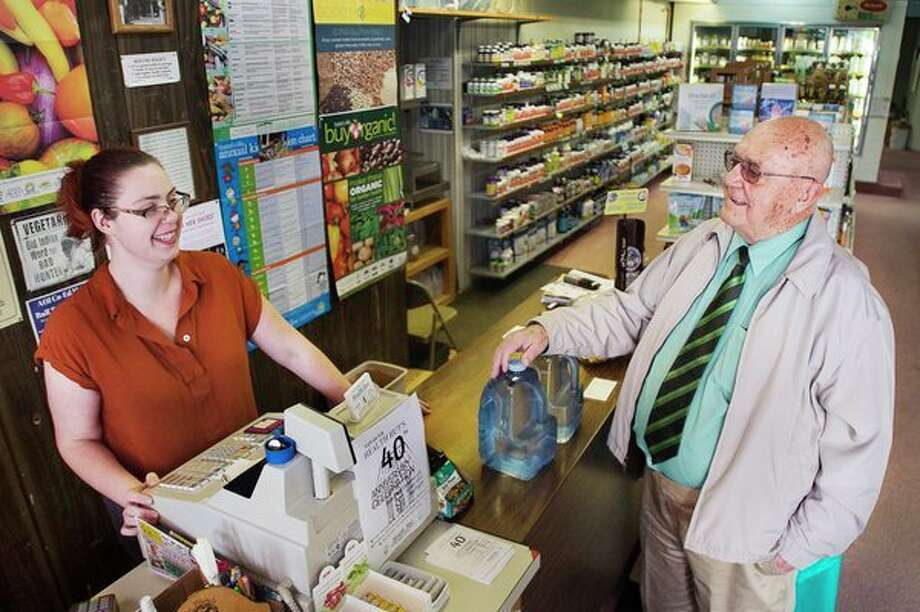 The Health Hut Manager Paige Fryzelka, left, listens as customer Bob Douponce, right, tells her a joke Monday inside the store. For more photos, visit www.ourmidland.com. (Katy Kildee/kkildee@mdn.net)