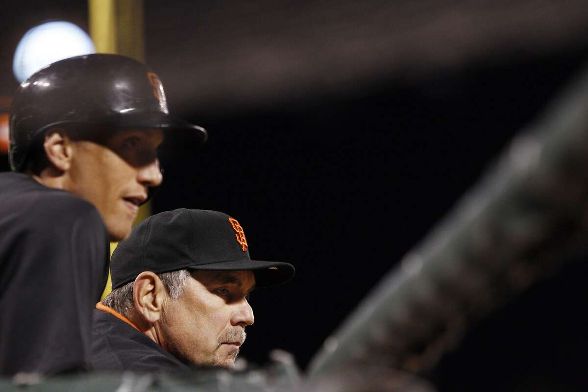 Bruce Bochy and Hunter Pence watch the game in the bottom of the ninth inning while trailing the Athletics. The San Francisco Giants played first home preseason game of the 2013 season against the Oakland Athletics at AT&T Park in San Francisco, Calif., on Thursday, March 28, 2013.