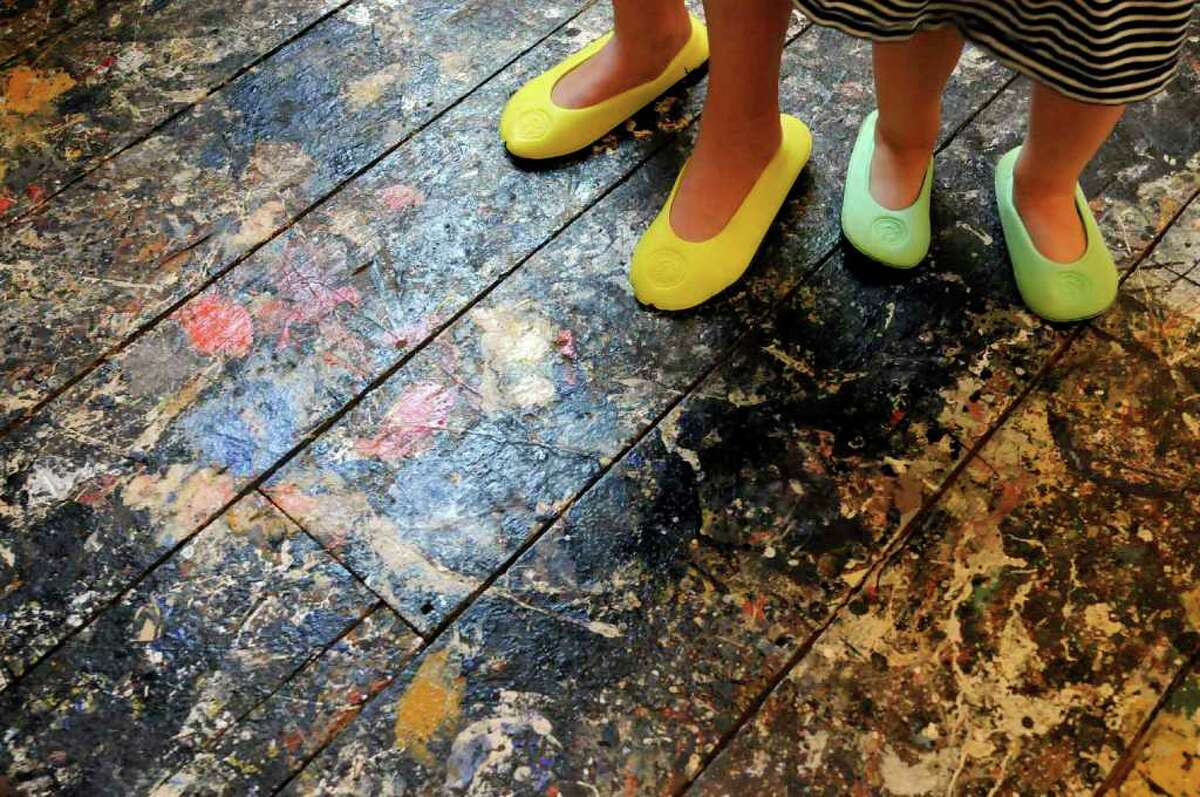 Foot coverings protect the floor during a tour of Jackson Pollock's paint-splattered studio at the Pollock-Krasner House and Study Center in East Hampton. (Michael P. Farrell / Times Union)