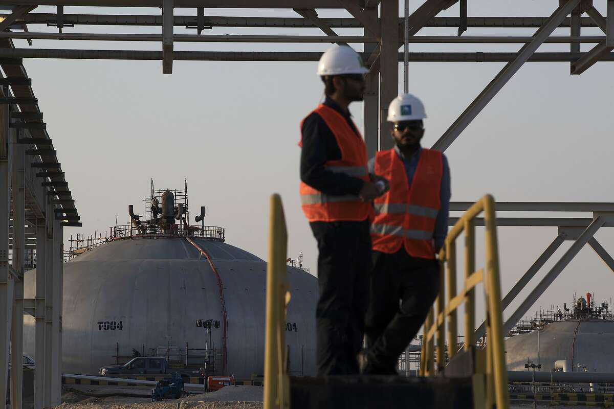 Employees stand near tanks at Saudi Aramco's Abqaiq crude oil processing plant following a drone attack in Abqaiq, Saudi Arabia, on Friday, Sept. 20, 2019. Saudi Aramcorevealed the significant damage caused by an aerial strike on its Khurais oil field and Abqaiq crude-processing plant last weekend, and insisted that the sites will be back to pre-attack output levels by the end of the month. Photographer: Faisal Al Nasser/Bloomberg