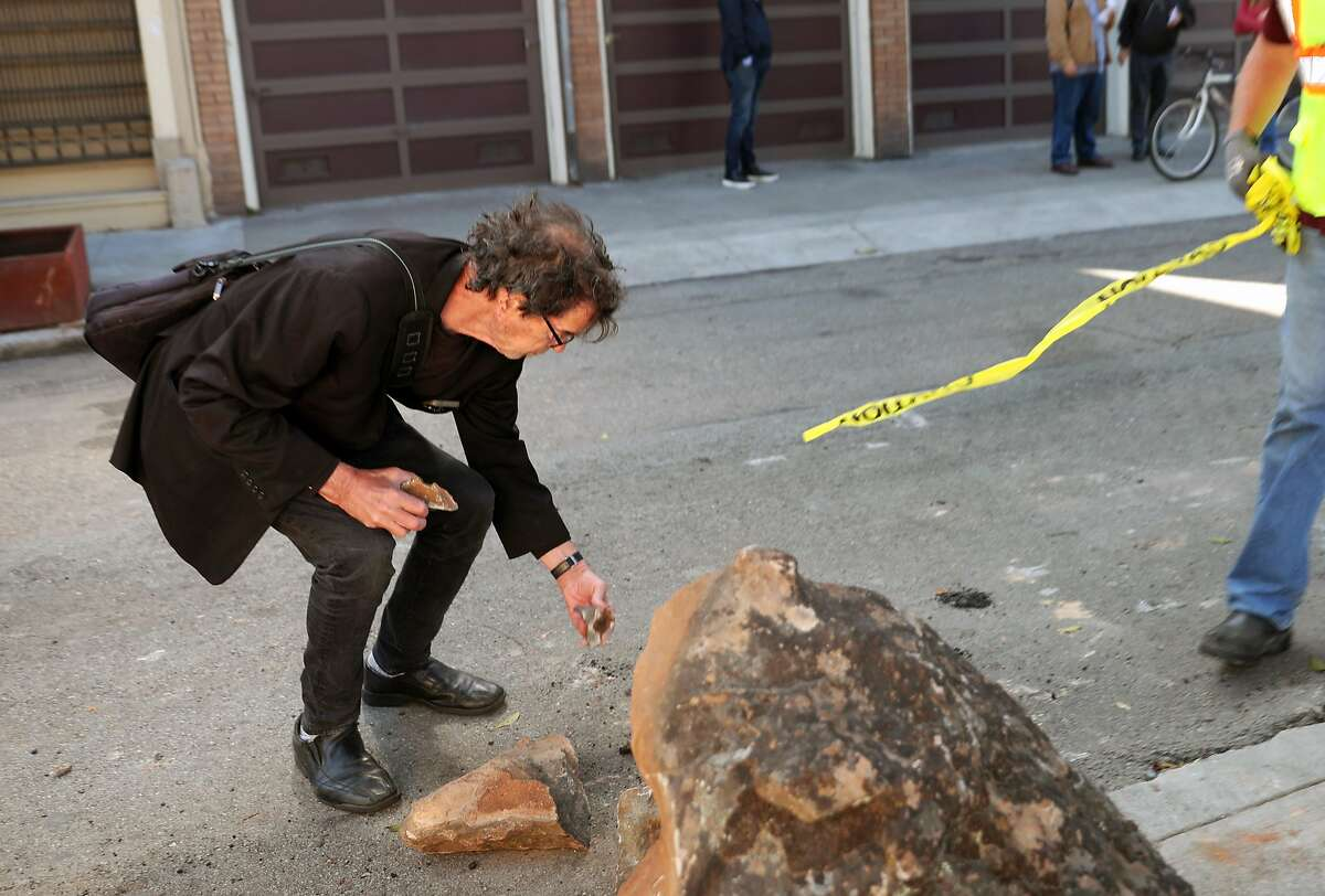 Richardd, a resident in the neighborhood, saves rock remnants from the boulders as public works removes them from the sidewalk along Clinton Park near Market at Dolores streets on Monday, Sept. 30, 2019, in San Francisco, Calif.