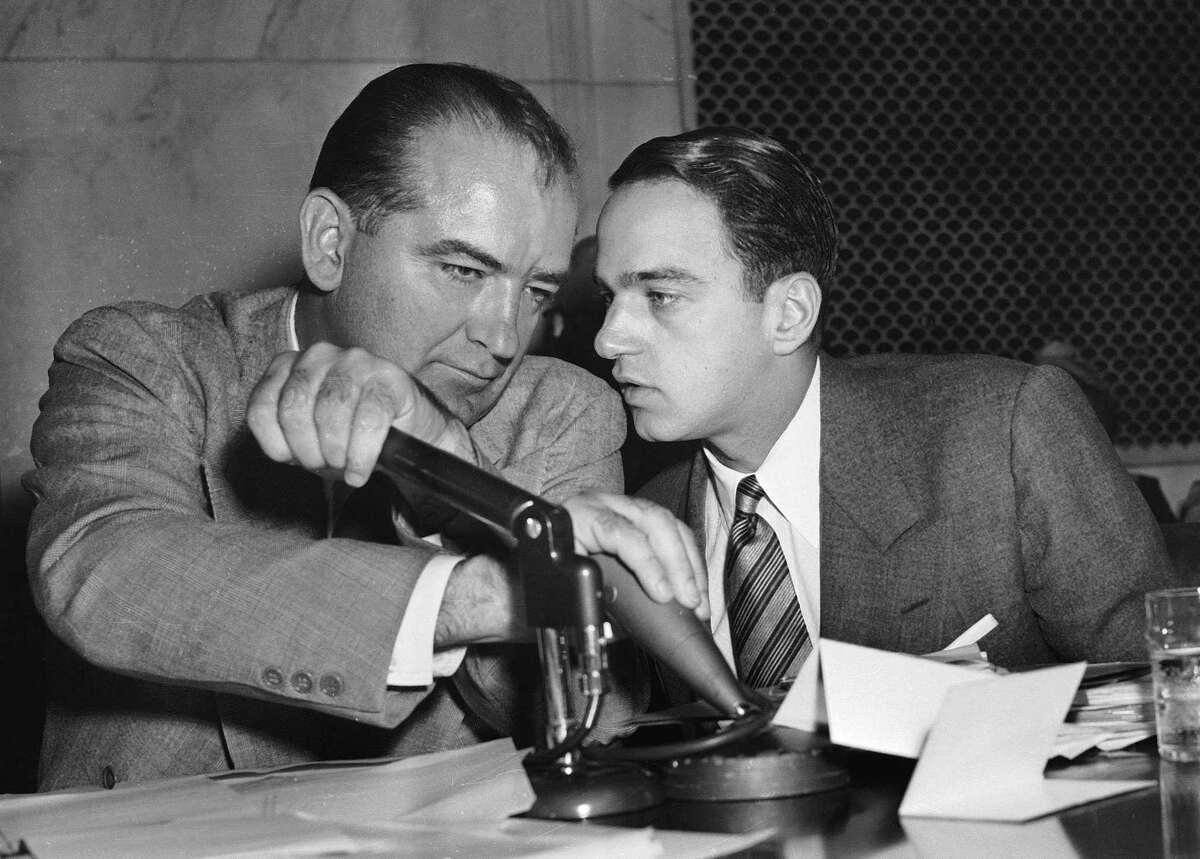 Joseph McCarthy covers the microphones with his hands while having a whispered discussion with his chief counsel, Roy Cohn, during a committee hearing in Washington in this April 26, 1954 file photo.