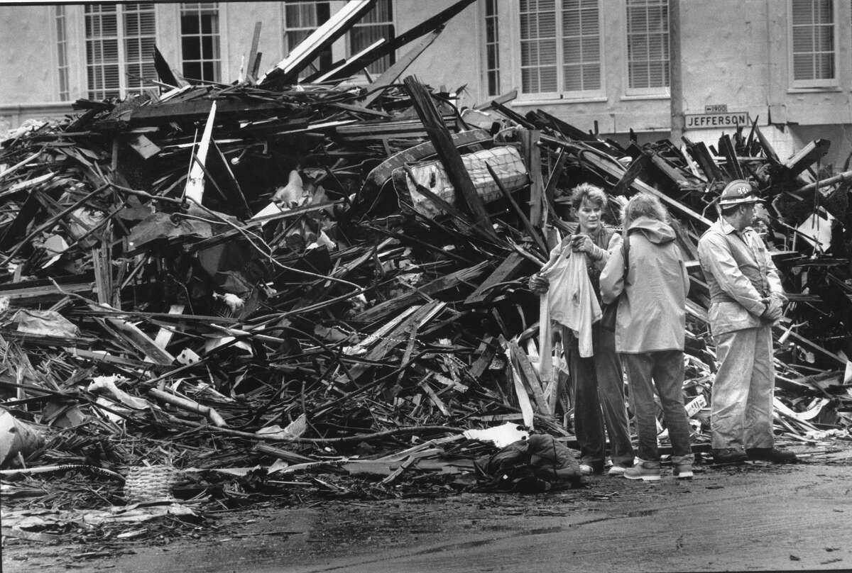 Residents of the Marina District go through rubble and find a sweater near a condemned building severely damaged by the Loma Prieta earthquake, Photo taken October 23, 1989