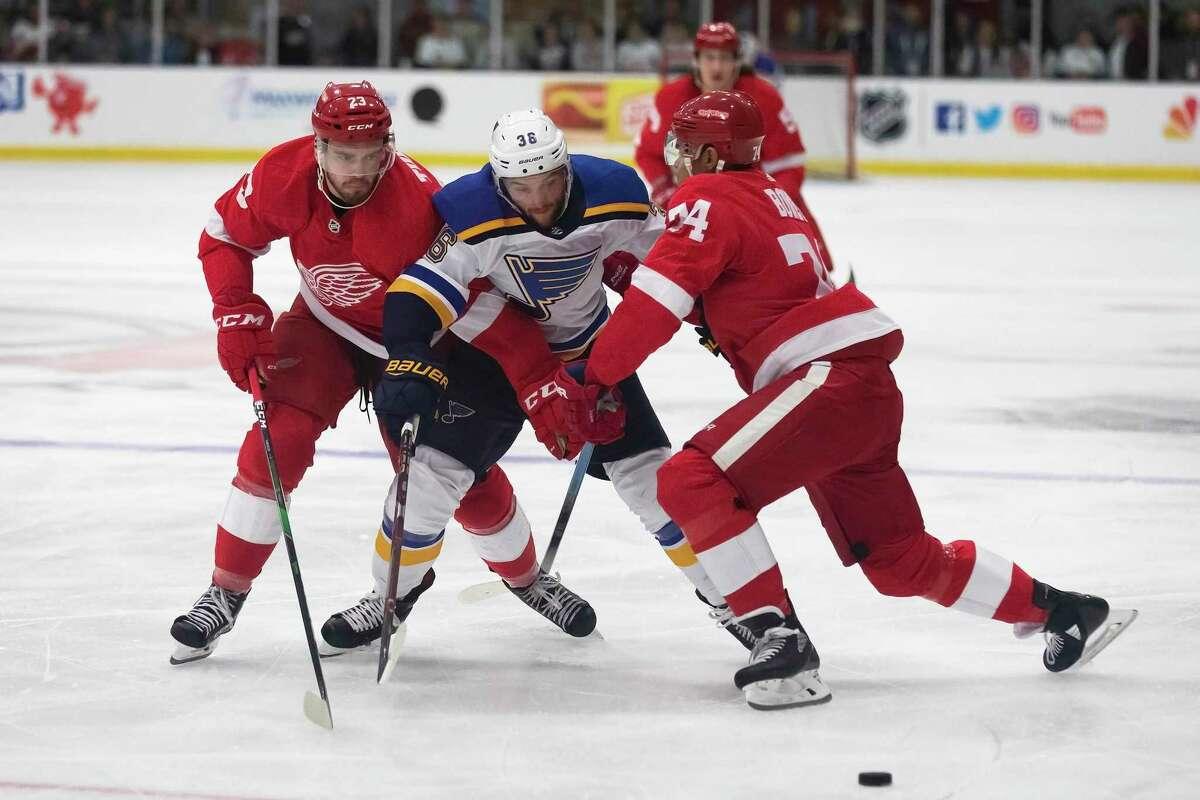 Detroit Red Wings forward Dominic Turgeon, left, and defenseman Madison Bowey, reach for the puck with St. Louis Blues forward Nathan Walker on Thursday, Sept. 26, 2019, during an NHL hockey preseason game in Calumet, Mich. The Blues will play the Washington Capitals in the first game of the 2019-20 season, on Oct. 2, 2019.