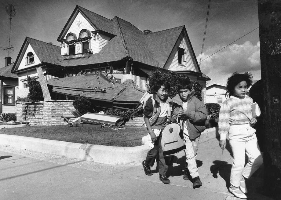Children walk by a home at the corner of 5th and Jefferson Ave. in Watsonville damaged by the Loma Prieta earthquake, October 26, 1989 Photo ran 11/2/1990, P 10, Briefing Photo: Scott Sommerdorf / The Chronicle