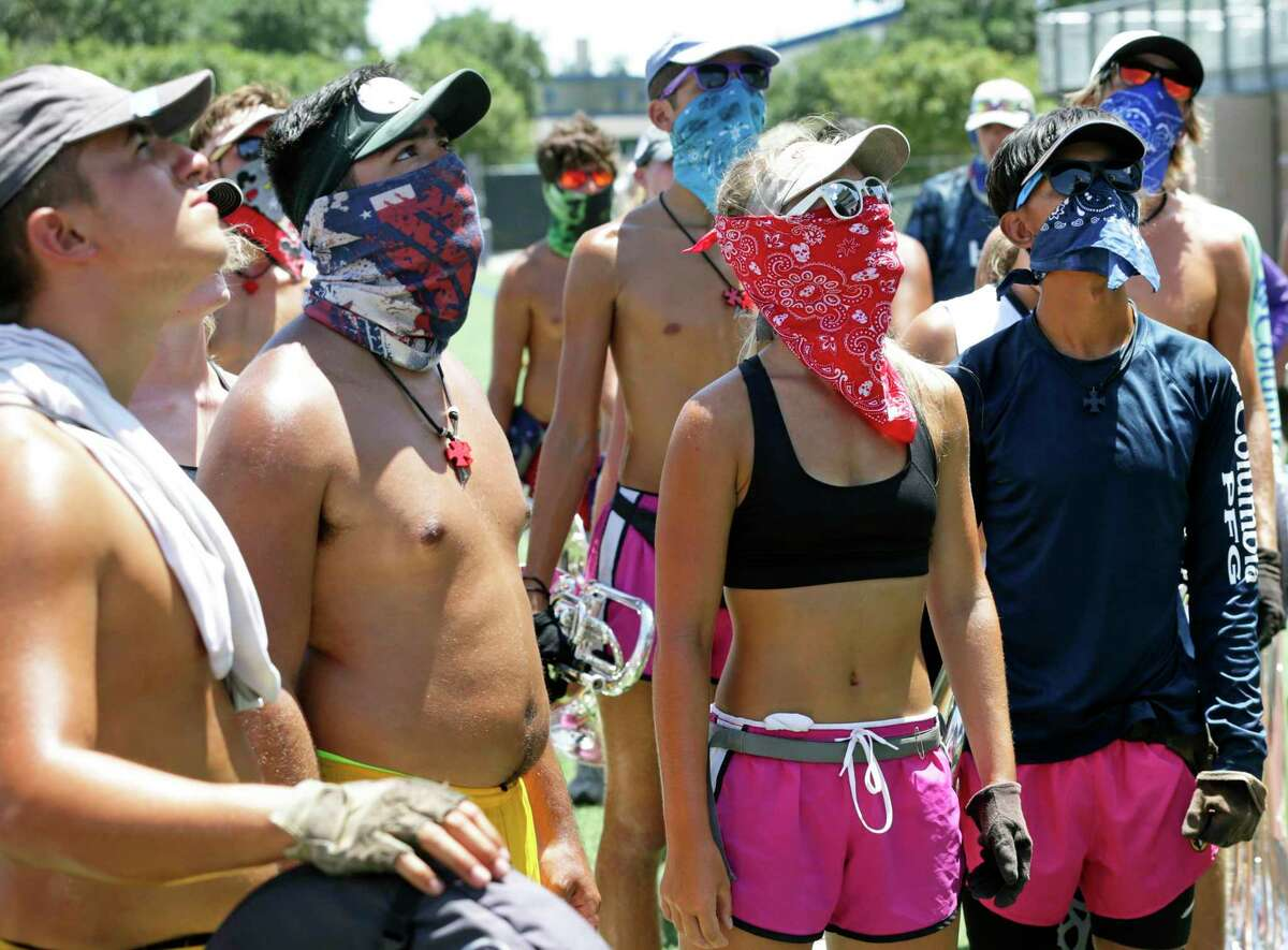 Maddie McCreight, center, stands with other members of the horns section of the Crossmen of San Antonio, some wearing scarfs to protect their faces from the sun, while they listen to their director as the practice at Farris Stadium on July 19. The heat in August and September broke numerous records here.