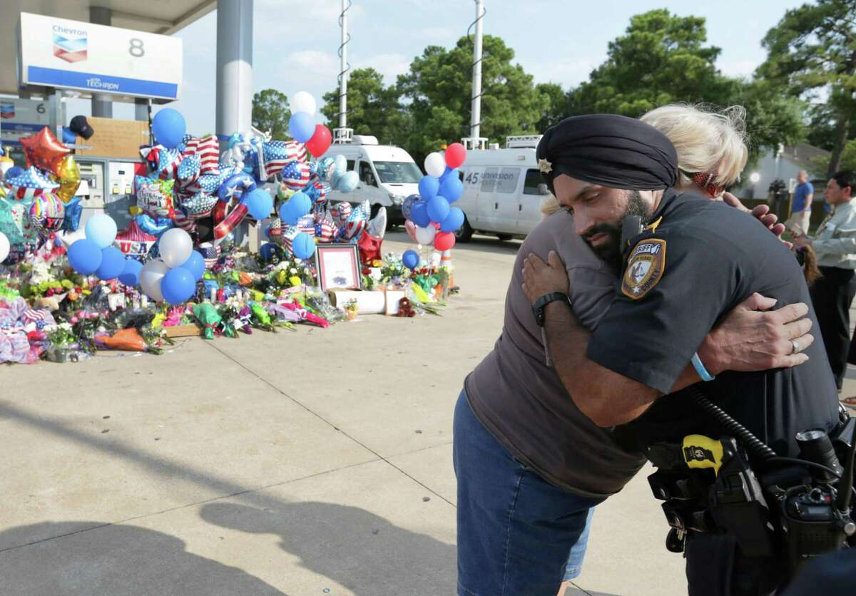 Harris County Sheriff's Deputy Dhaliwal gets a hug from Janet Waldrep at a memorial for Deputy Darren Goforth, at the Chevron where he was killed, Sunday, Aug. 30, 2015, in Houston. Deputy Dhaliwal was one of the first deputies on the scene of the shooting. ( Jon Shapley / Houston Chronicle )