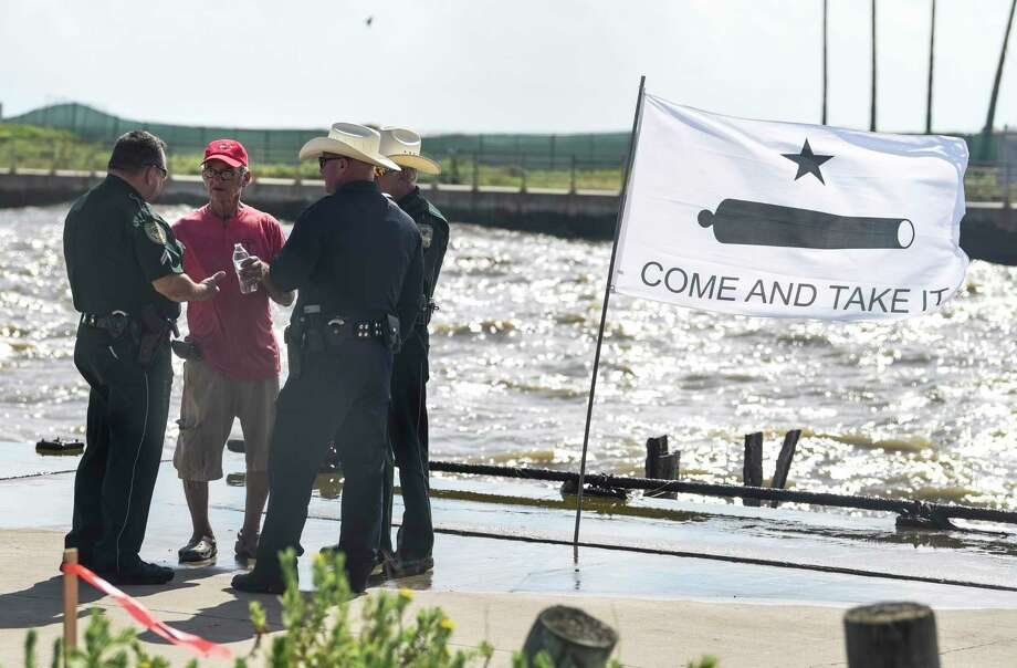 Ted Vega talks to Galveston County Sheriff's officers as they try to get him to leave the Rollover Pass in Bolivar Peninsula Monday afternoon as construction crew put up fence to keep people out. Vega was eventually arrested for trespassing since he refused to leave.