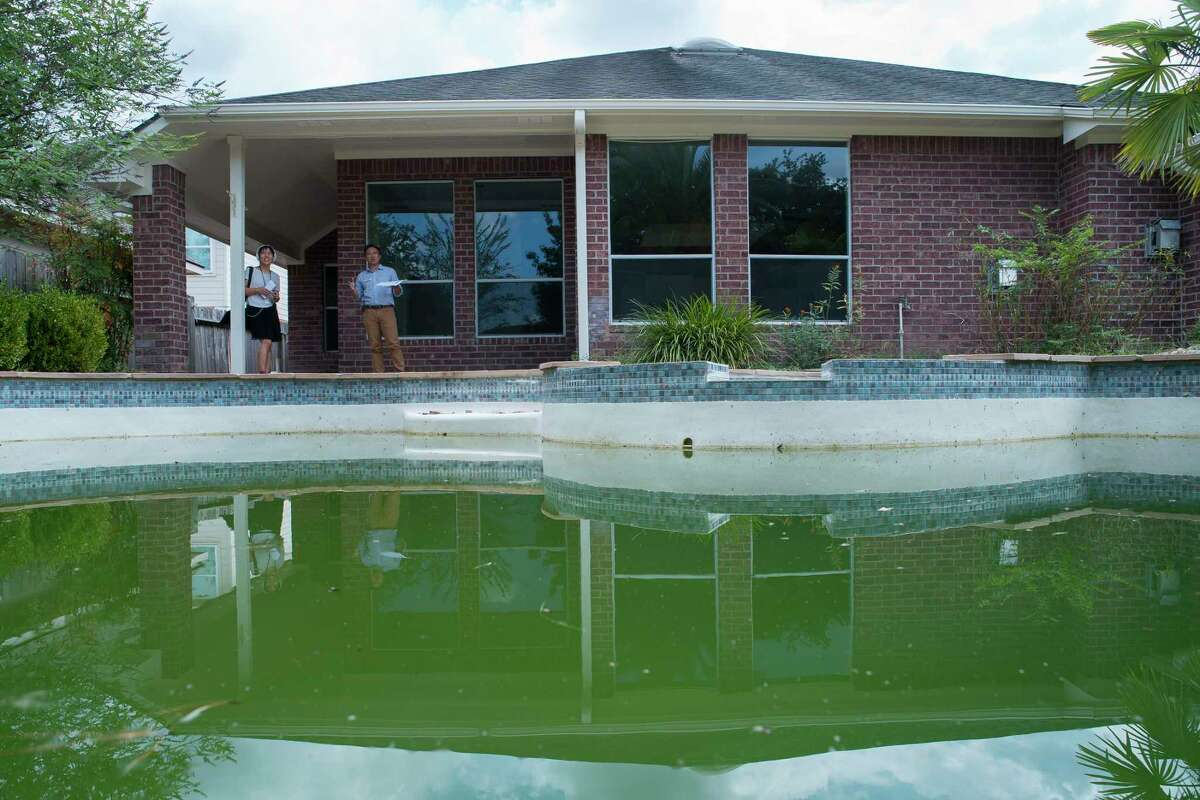 Green water fills a pool on a partially remodeled home in the Wimbledon Champions neighborhood in Spring, Monday, Sept. 16, 2019. Several homes in the area have been purchased by investors after Harvey and are in various states of repair from fully remodeled to currently in foreclosure.