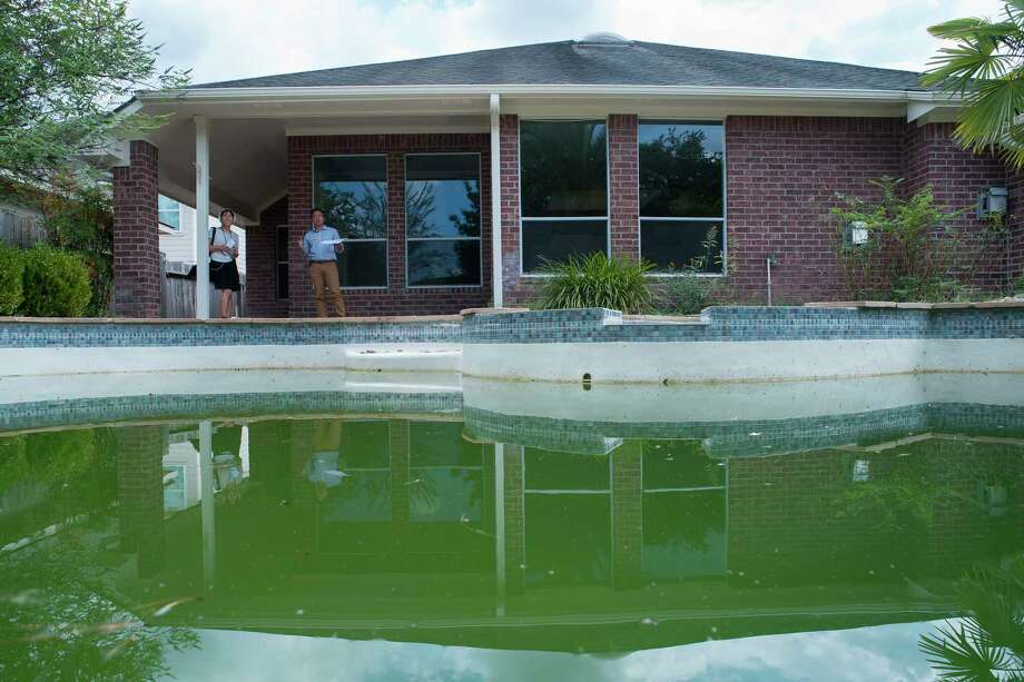 Green water fills a pool on a partially remodeled home in the Wimbledon Champions neighborhood in Spring, Monday, Sept. 16, 2019. Several homes in the area have been purchased by investors after Harvey and are in various states of repair from fully remodeled to currently in foreclosure. Photo: Mark Mulligan, Houston Chronicle / Staff Photographer / © 2019 Mark Mulligan / Houston Chronicle