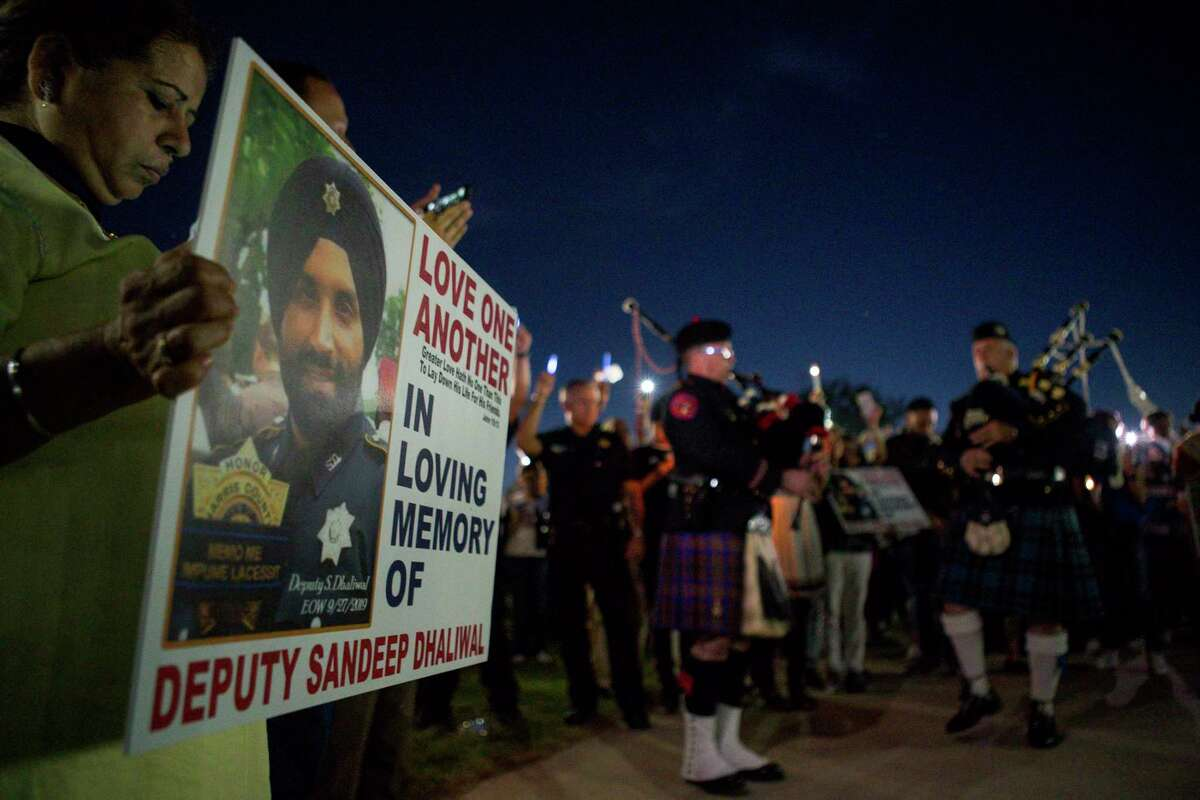 """Bagpipers play """"Amazing Grace"""" at the conclusion of a vigil for Harris County Sheriff's Office Deputy Sandeep Dhaliwal at Harris County Deputy Darren Goforth Park in northwest Houston, Monday, Sept. 30, 2019."""