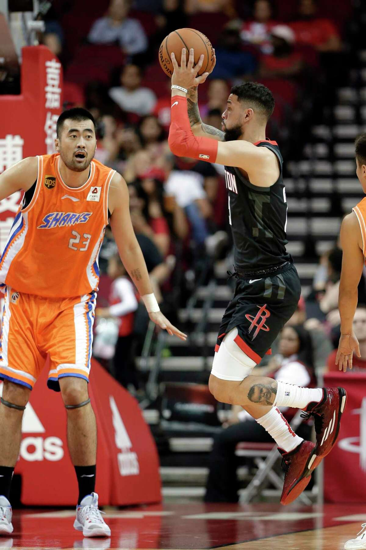 Shanghai Sharks center Zhang Zhaoxu (23) watches as Houston Rockets guard Austin Rivers, right, passes the ball during the first half of an NBA basketball preseason game Monday, Sept. 30, 2019, in Houston. (AP Photo/Michael Wyke)
