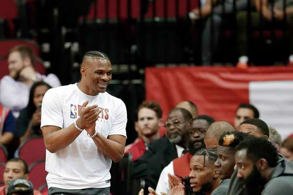 Houston Rockets guard Russell Westbrook, left, celebrates a score from the bench as he sits out an NBA basketball preseason game against the Shanghai Sharks during the first half Monday, Sept. 30, 2019, in Houston. (AP Photo/Michael Wyke)