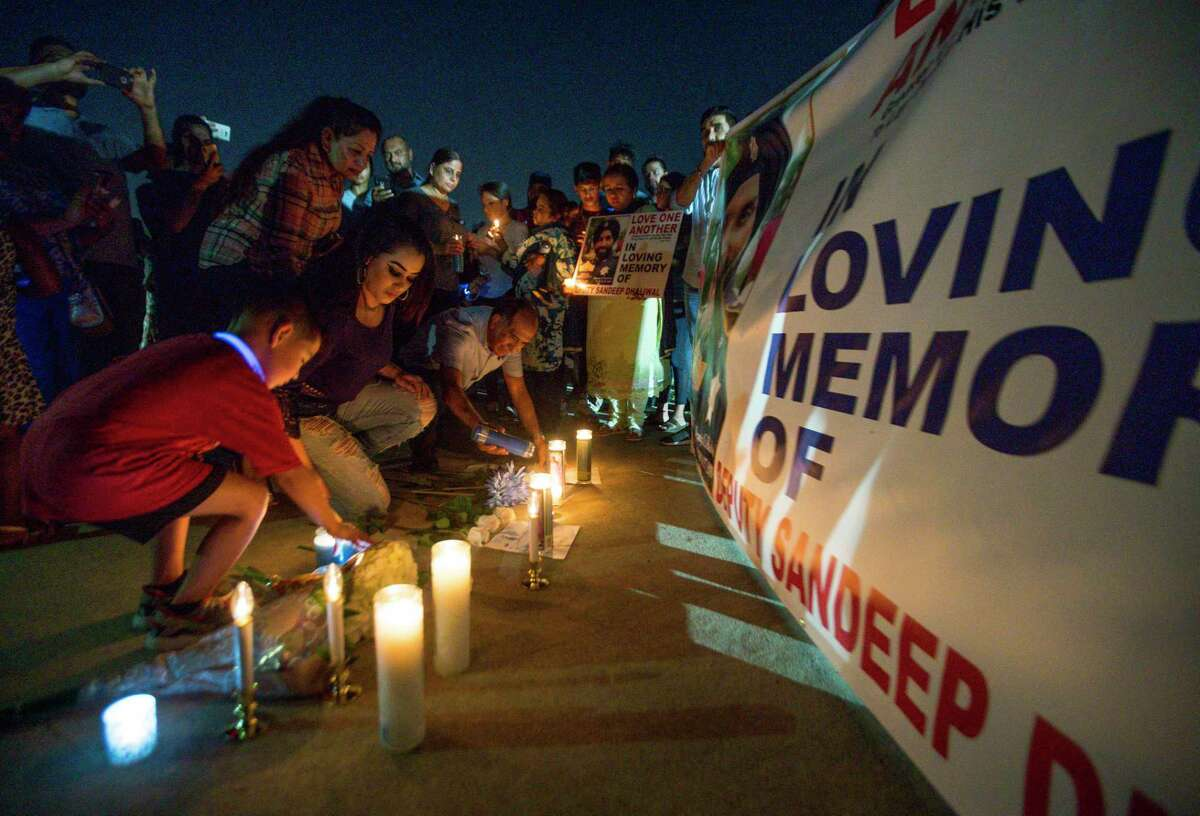 People lay candles in front of a poster following a vigil for Harris County Sheriff's Office Deputy Sandeep Dhaliwal at Harris County Deputy Darren Goforth Park in northwest Houston, Monday, Sept. 30, 2019.