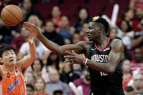 Houston Rockets center Clint Capela, right, passes the ball over Shanghai Sharks guard Shi Yuchen (11) during the second half of an NBA basketball preseason game Monday, Sept. 30, 2019, in Houston. (AP Photo/Michael Wyke)