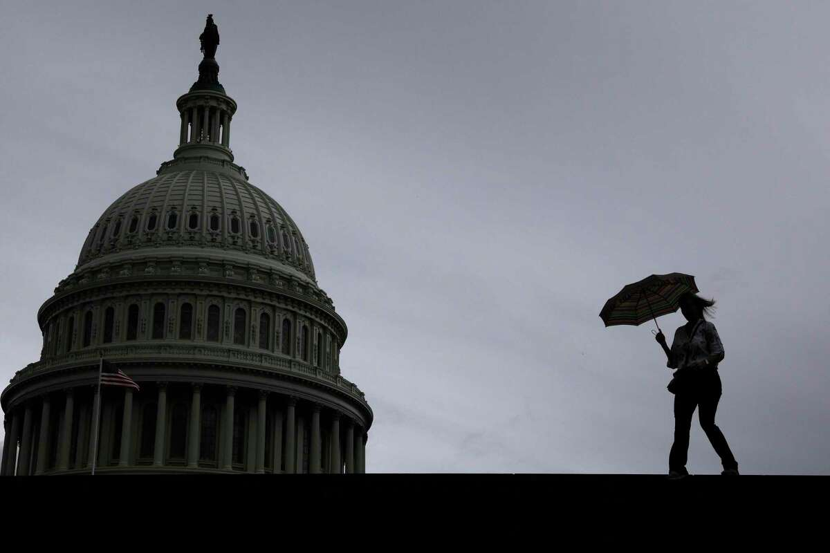 A visitor walks across the east front of the U.S. Capitol during a rain storm, on Monday on Capitol Hill in Washington, D.C. Select Congressional committees will return to the Capitol to continue impeachment proceedings throughout the week as Congress remains on recess.