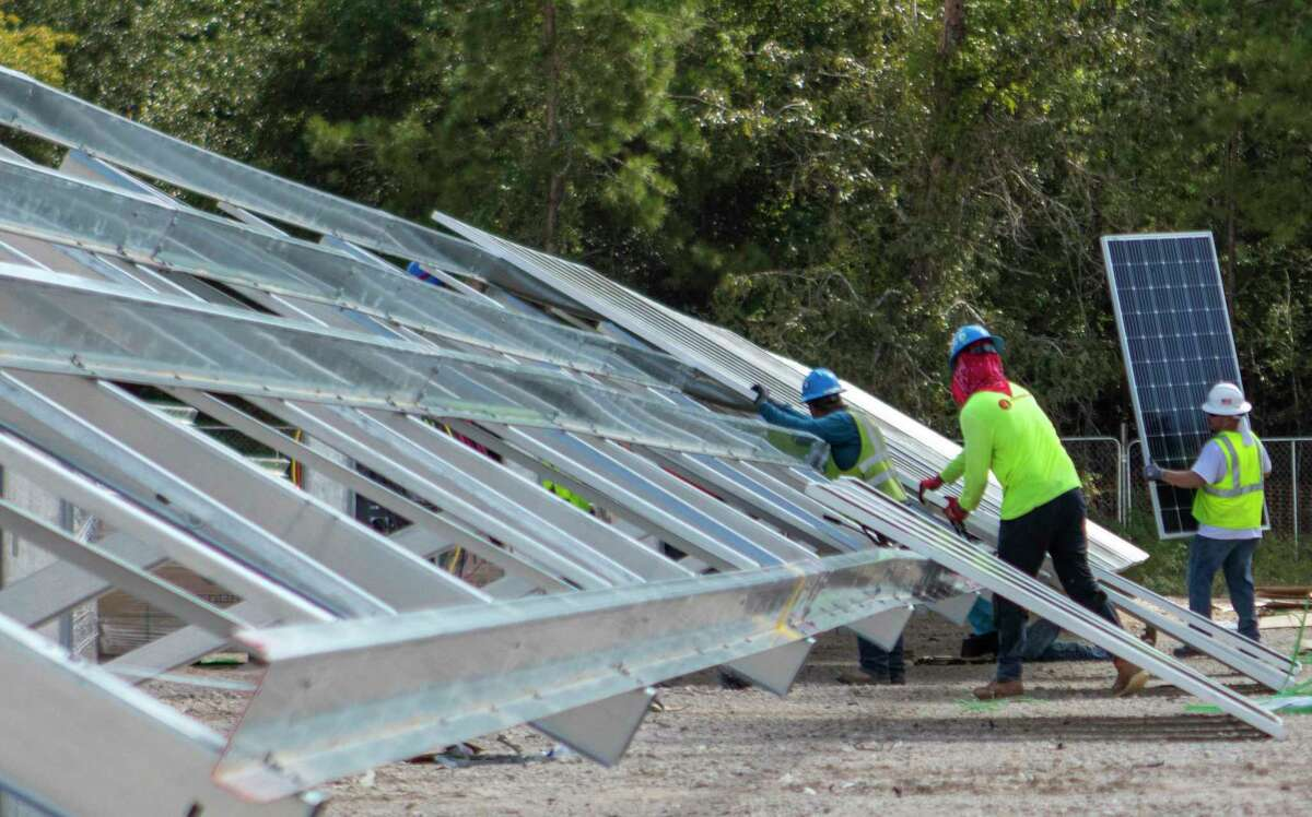 Construction workers install solar panels onto framing Thursday, September 26, 2019 at the construction site for Stockton Junior High School in Conroe.