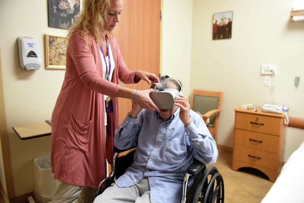 Kristen Pidgeon, therapeutic recreation manager at Schenectady Center nursing home, puts a virtual reality headset on Arthur Graham, 97, a resident at the center, on Tuesday, Oct. 1, 2019, in Schenectady, N.Y. (Will Waldron/Times Union)