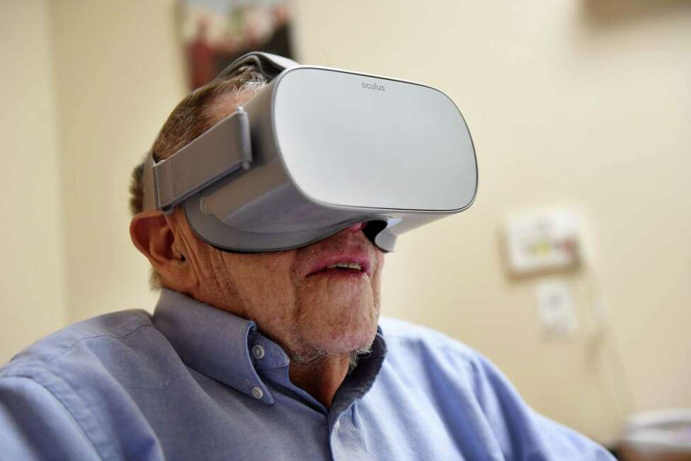 Arthur Graham, 97, a resident at the Schenectady Center nursing home, tries on some virtual reality glasses for an immersive experience in the confines of his room on Tuesday, Oct. 1, 2019, in Schenectady, N.Y. (Will Waldron/Times Union)