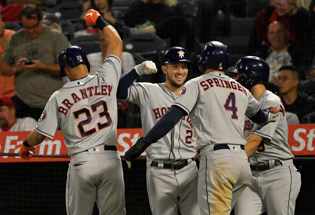Michael Brantley #23 of the Houston Astros celebrates with team mates Alex Bregman #2, George Springer #4 and Jose Altuve #27 after hitting a three run home run against pitcher Luis Garcia #40 of the Los Angeles Angels in the eighth inning at Angel Stadium of Anaheim on Sept. 27, 2019 in Anaheim, California.