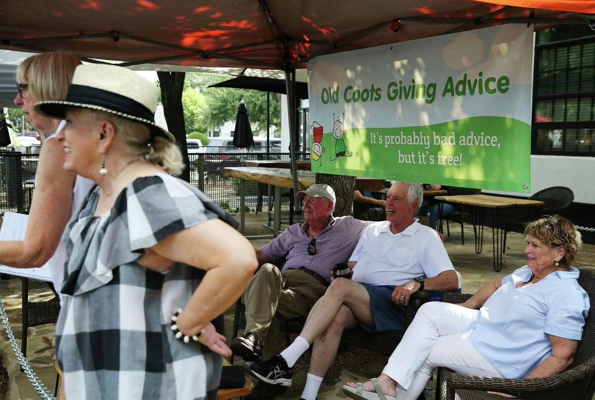 The Old Coots wait for shoppers at the New Braunfels Farmers Market to ask for their advice. The booth is one of the most popular at the market. Even people who don't have a question often ask if they can take a picture of the group.