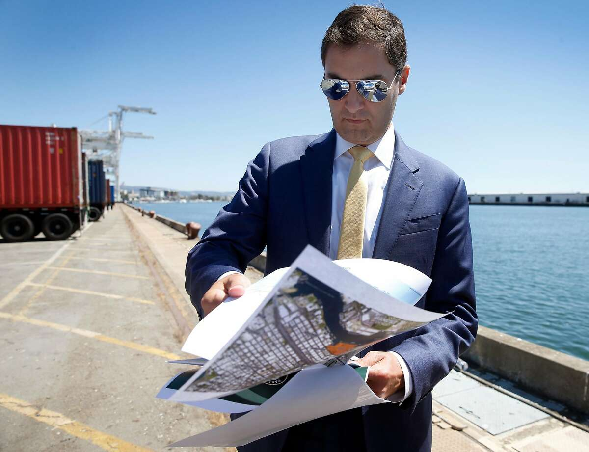 Oakland A's President Dave Kaval flips through renderings of the development plan while leading a private tour of the Howard Terminal site in Oakland, Calif. on Tuesday, Sept. 3, 2019 where the baseball team is hoping to build its new stadium.