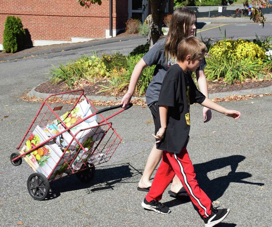 Spectrum/ The annual Walk a Mile for a Meal event was held Sept. 29, 2019 in New Milford to benefit Social Services. Families, individuals, civic groups, schools, businesses and others purchased a bag of groceries at co-sponsor Big and walked one mile to the parking lot behind the First Congregational Church at 36 Main St., where church members served beverages and snacks for walkers. Last year, the food bank gave out more than 8,000 bags of non-perishables to local households. Above, Savannah and Michael Harcor, 11 and 9, respectively, were the first ones to deliver non-perishables to the drop-off location. Photo: Deborah Rose / Hearst Connecticut Media / The News-Times  / Spectrum
