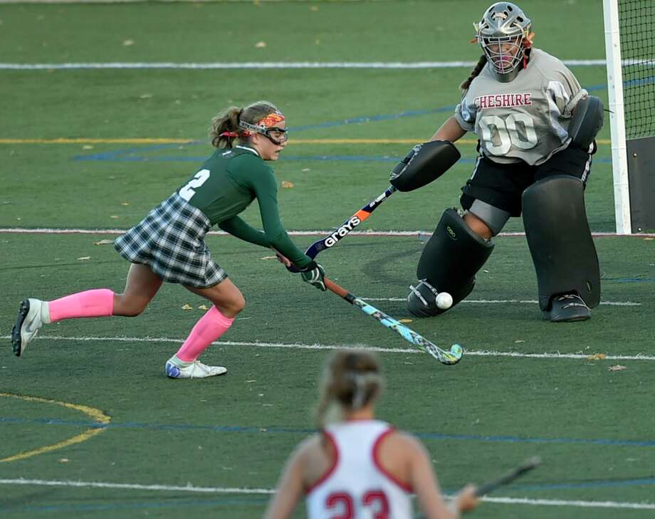 Guilford's Ella Stanley, left, looks to score against Cheshire goalie Alexis Hemstock during the SCC field hockey championship. Photo: Peter Hvizdak / Hearst Connecticut Media / New Haven Register