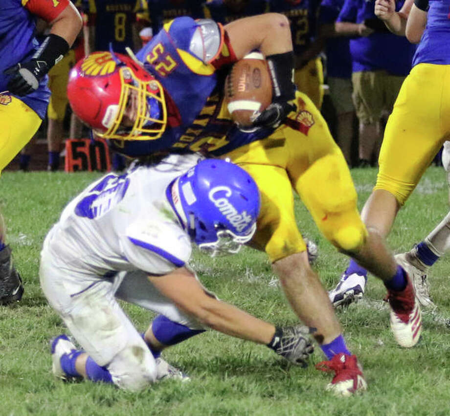 Roxana running back David Pluester (25) is tackled by Greenville's Tommy Baker in the second half Friday night at Raich Field in Roxana.