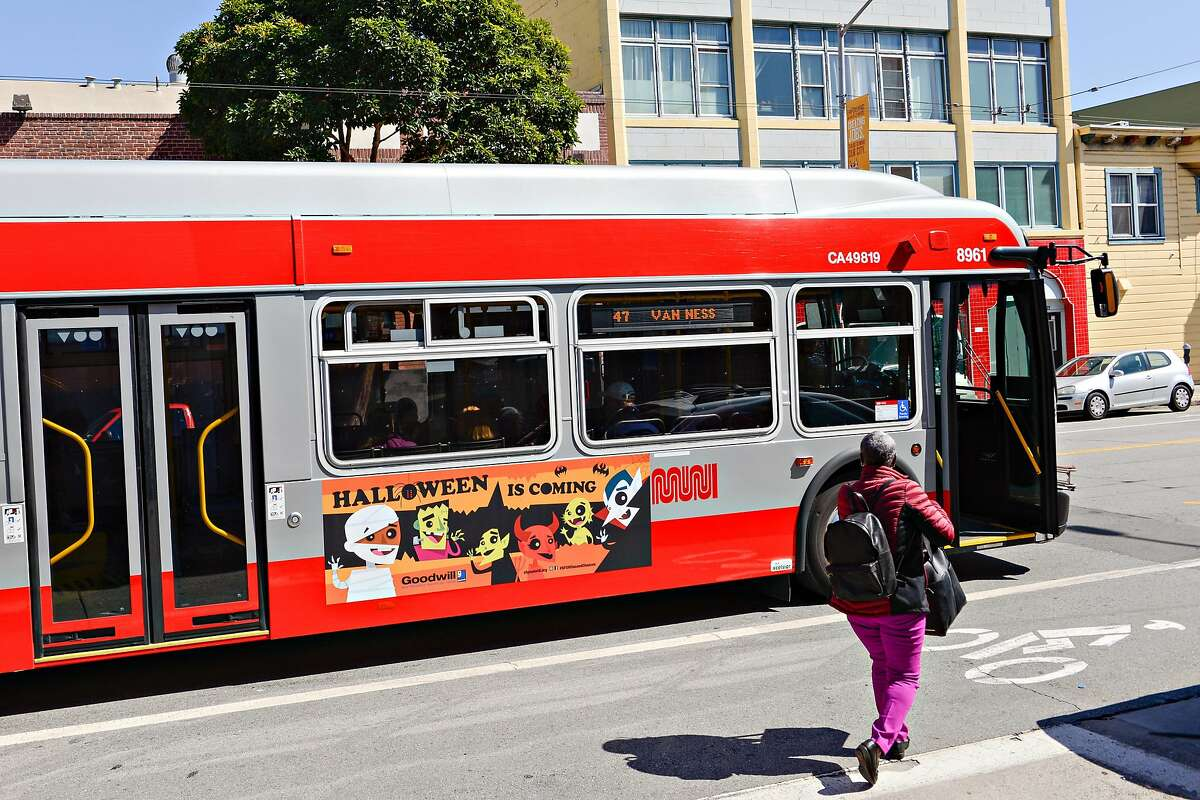 A woman boarding an all-electric Muni bus in the green zone at Howard and 11th Street where the bus switches to an all-electric operation in a part of the city that has been historically been overlooked for environmental equity on September 29, 2019 in San Francisco, Calif.
