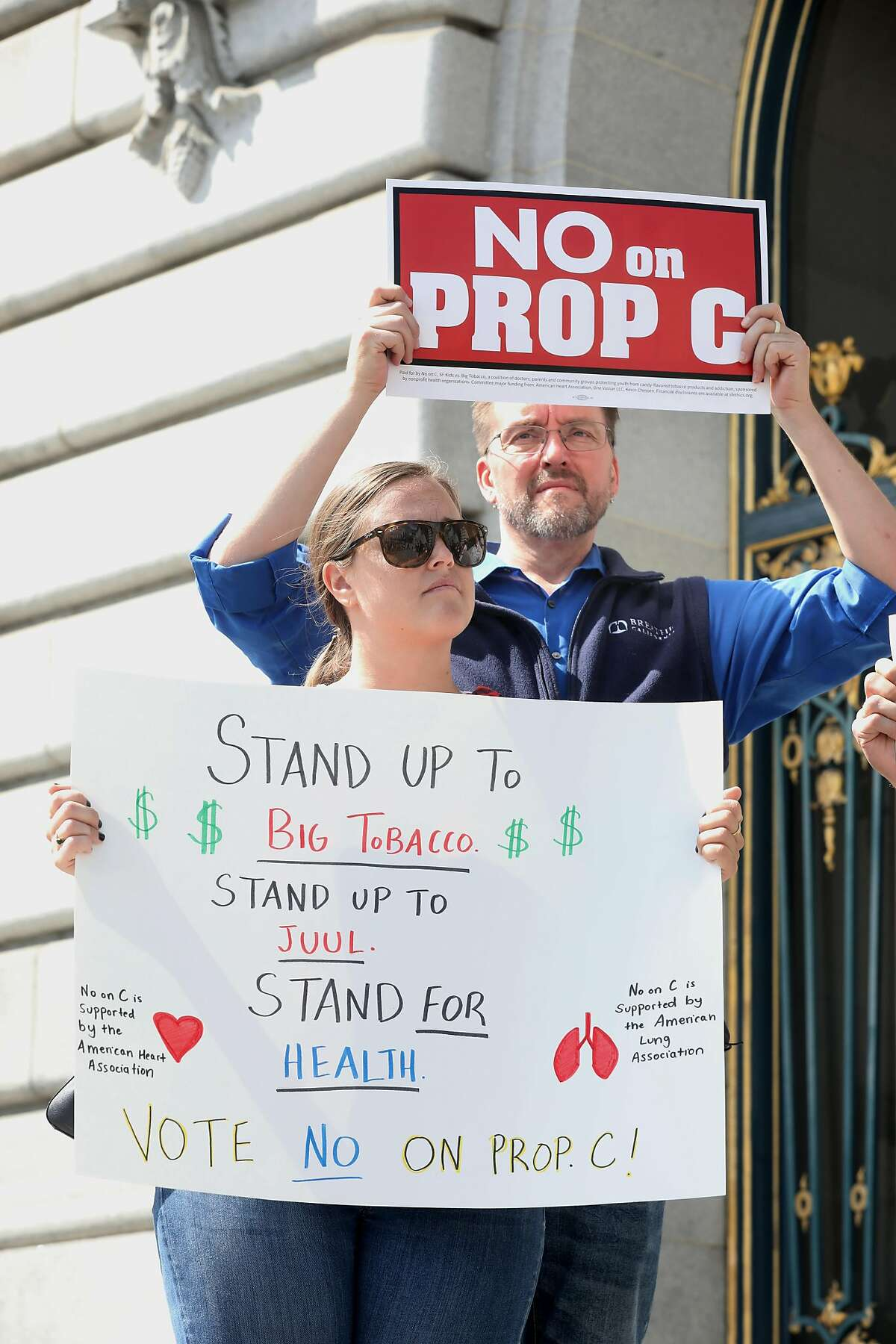 Jennifer Smutz (front) from the American Heart association and Brian Sawyer (back) from Breathe California protest at the SF Kids vs Big Tobacco rally, the public health groups opposing Juul�s ballot initiative called The No on C campaign, as they kick-off an event outside City Hall on Wednesday, Sept. 4, 2019 in San Francisco, Calif.