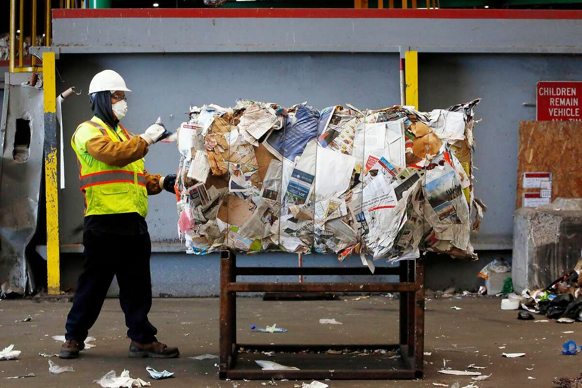 Allen Maculangan, material handler, removes plastic bags from bales of paper, one of the many steps San Francisco is taking to manage single use plastics, at Recology's Recycle Central on Monday, September 30, 2019 in San Francisco, CA.